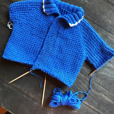 Fisherman's baby sweater on needles