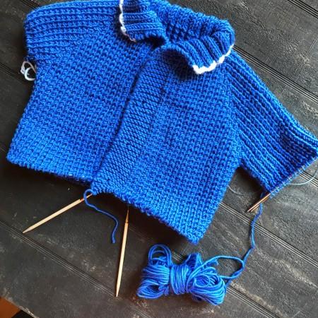 Fisherman's baby sweater on needles